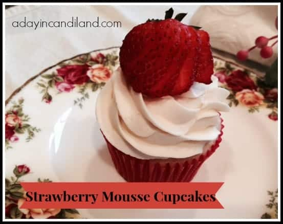 Strawberry Cupcakes with filling on a china plate with a sliced strawberry on top