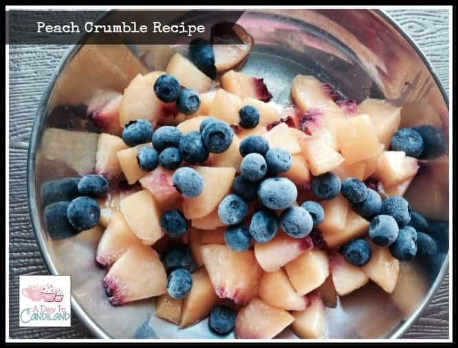 Chopped peaches and blueberries in dish for peach cobbler