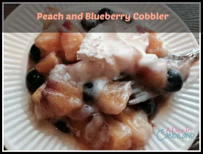White plated dish of peach cobbler with blueberries and whipping cream a quick and delicious dessert