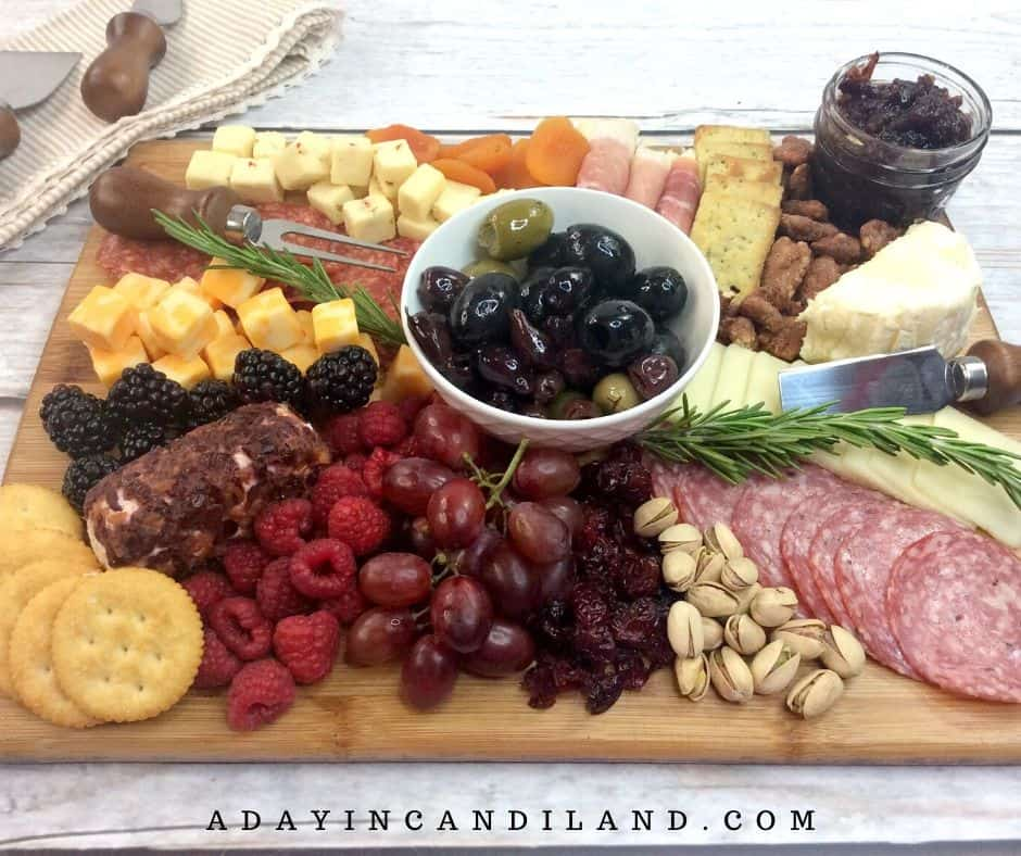 Fruit, olives, meats, cheeses and nuts on a board.