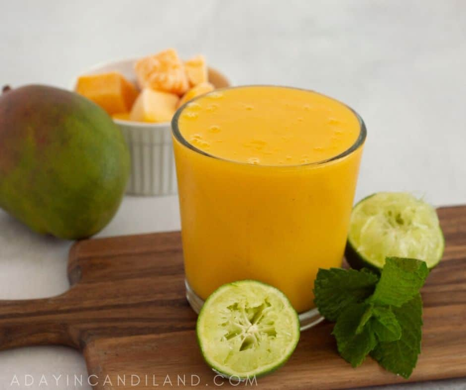 Glass of Mango Smoothie with a Mango, limes and mint leaf.
