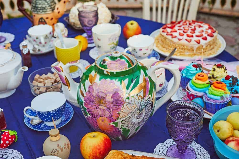 A table full of colorful dishes and set up for tea