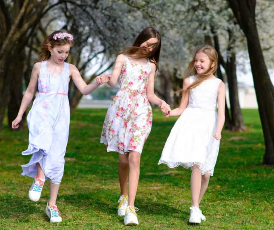 3 girls dress up for tea holding hands in the park