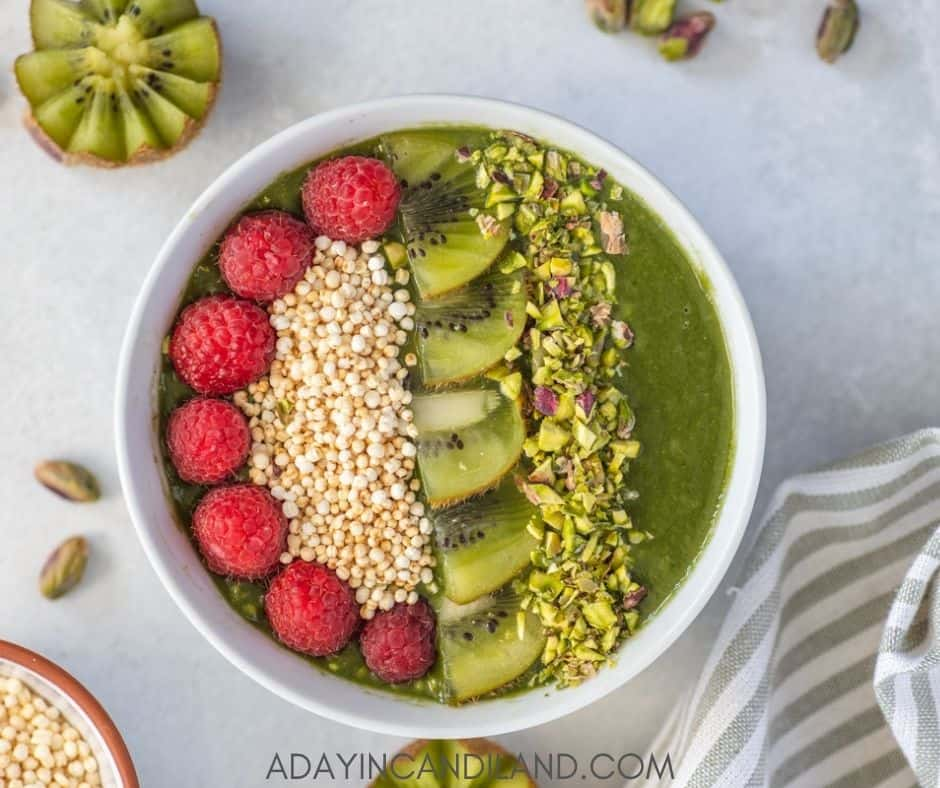 Green Smoothie Bowl with a striped napkin, and kiwi on the table.