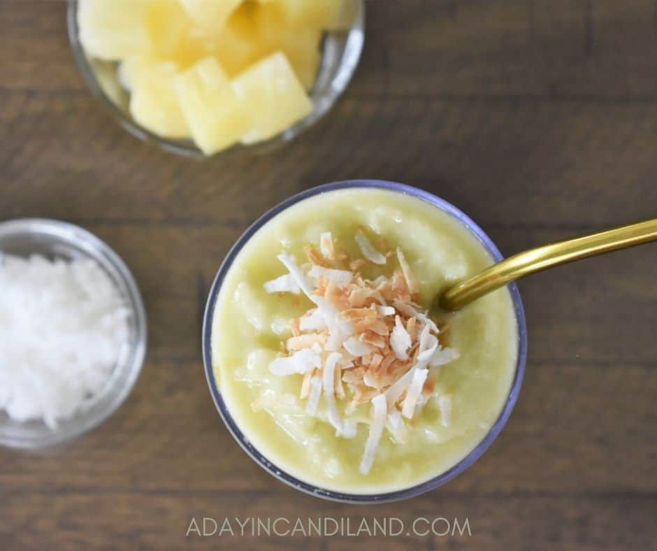 Top angle of Pineapple smoothie with gold metal straw